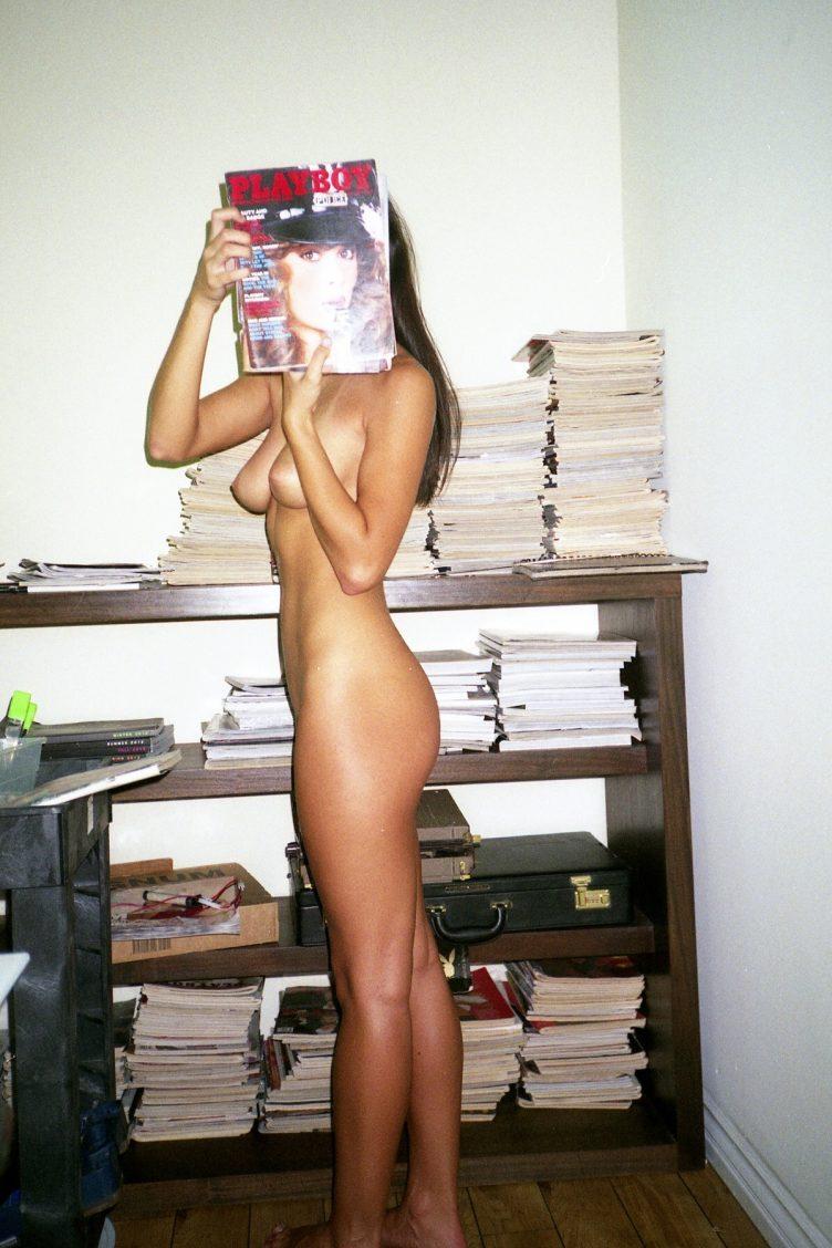 Nude girl reading Playboy magazine